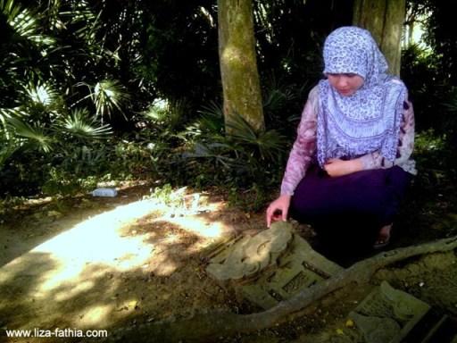 sebuah nisan yang berbentuk balok dan terdapat ornamen cermin, sulur, dan kaligrafi arab tergelat begitu saja di atas tanah dan patah terkena akar pohon. Lokasi : Lamcot, Darul Imarah, Aceh Besar