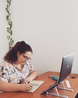 Copywriter-trabajando-mesa-escritorio-ordenador-boli-papel-libreta-gafas