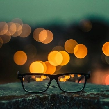Black-framed eyeglasses sitting on a rock with lights in the background.