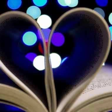 An open book with the pages folded in to forma  heart with lights in the background.
