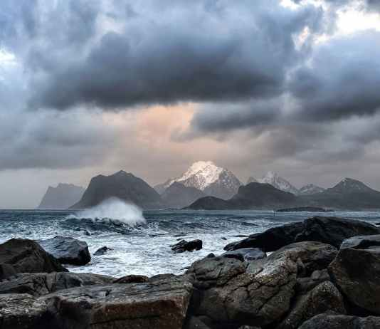 scenic view of snow capped mountains from across the rocky seashore