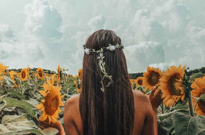 photo of woman near sunflowers