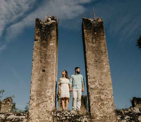 couple standing at destroyed stone pillars