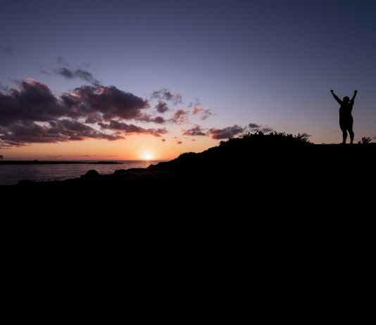 silhouette of person raising hands