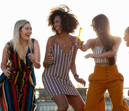 laughing young diverse girlfriends dancing and drinking beer during event