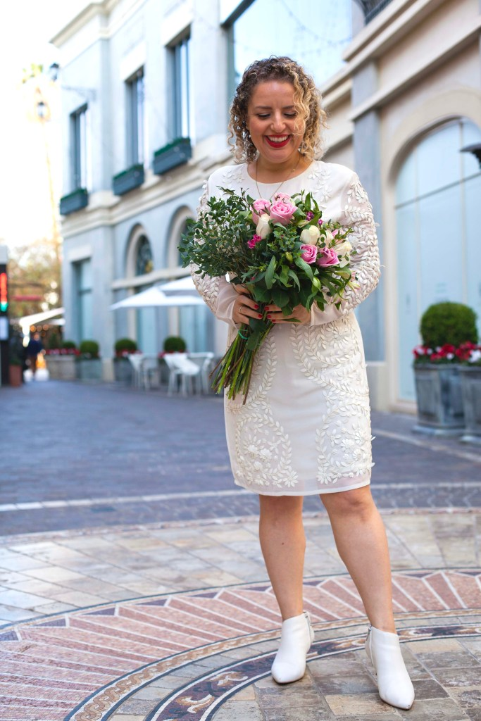 What to Wear on Valentine's Day, a blog post by Liz in Los Angeles, Los Angeles Lifestyle Blogger: an image of a blonde woman wearing a white dress holding flowers