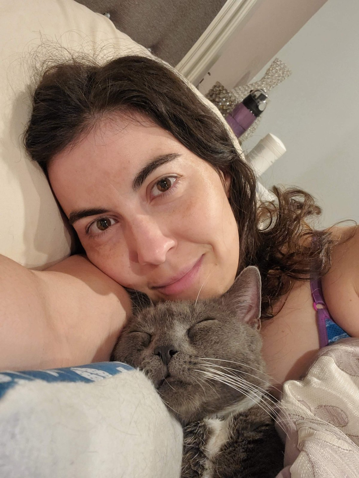 Woman cuddling grey cat