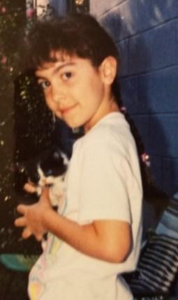 Girl holding tuxedo kitten