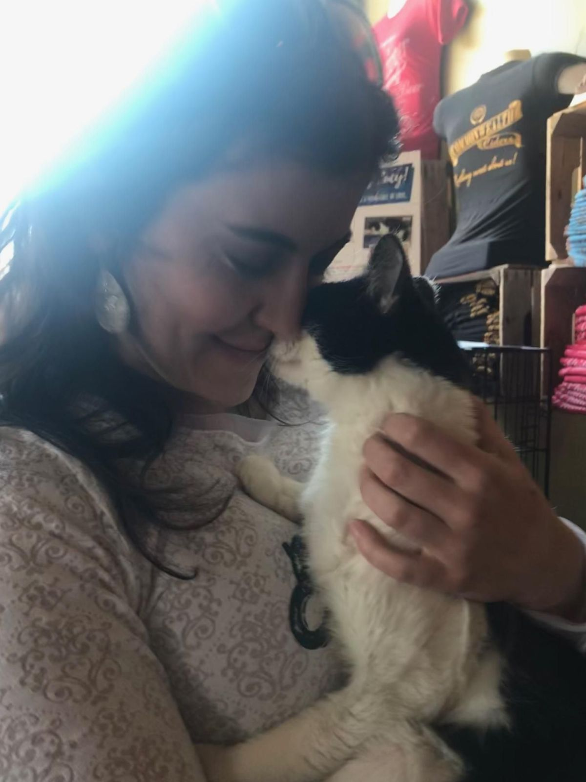 Woman snuggling black and white female cat