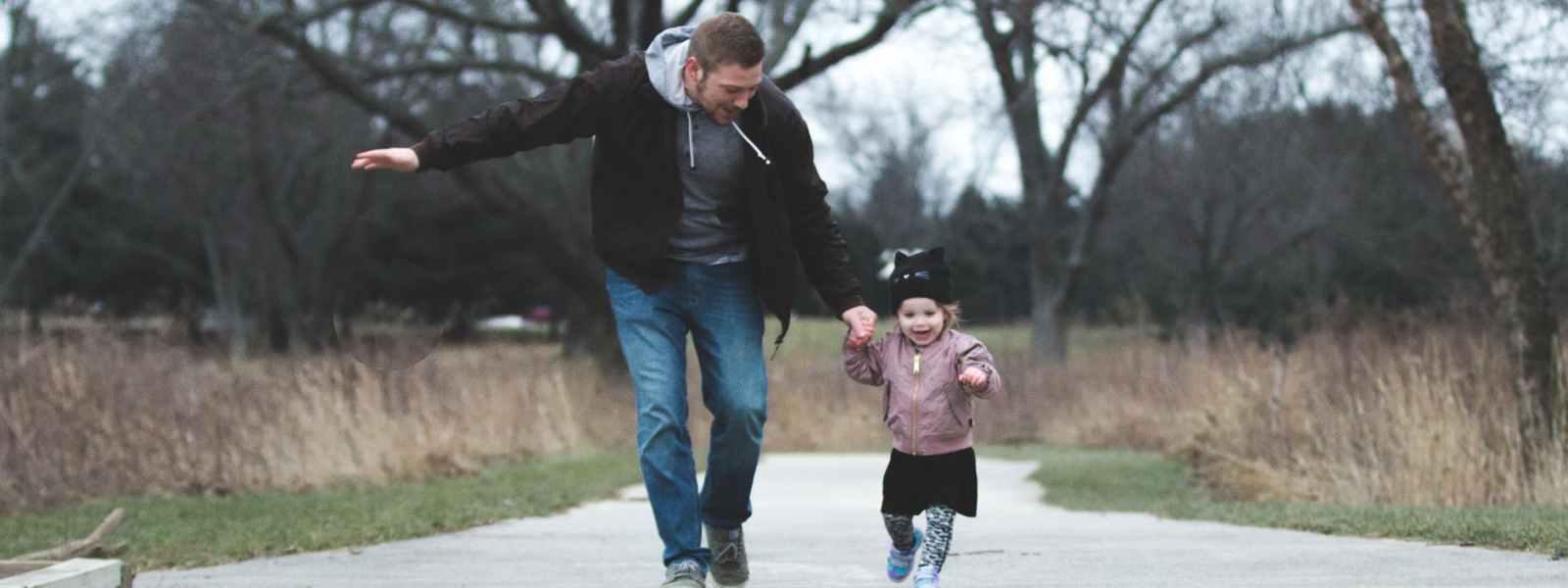 man and girl running on asphalt road