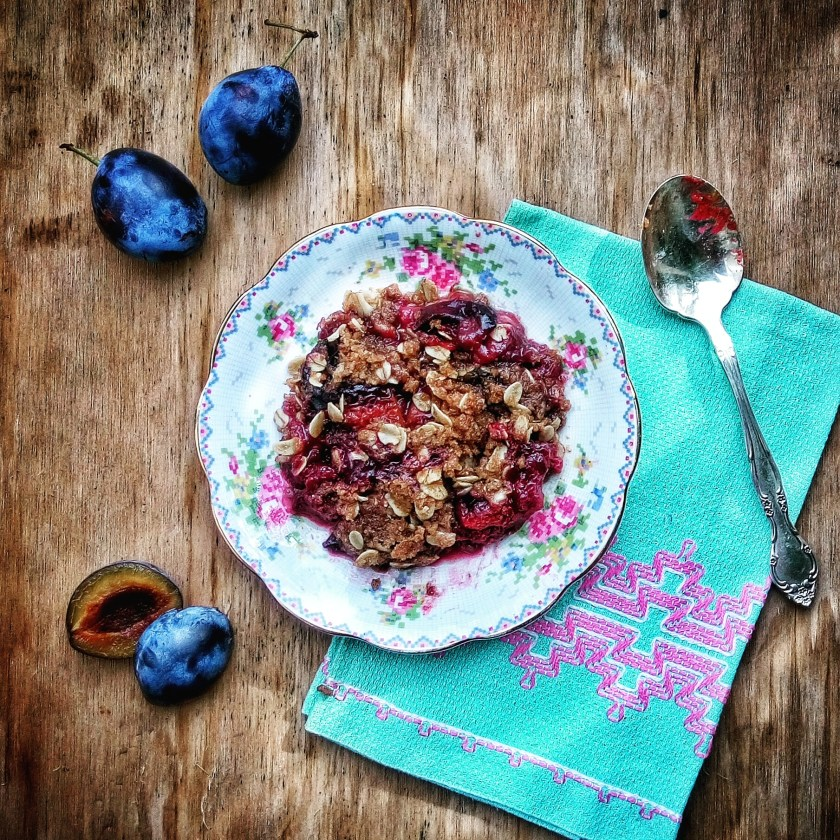 A quick and easy homemade plant-based plum crisp on antique plate with crossed stiched cloth napkin. Recipe by Lizzie Homemaker.
