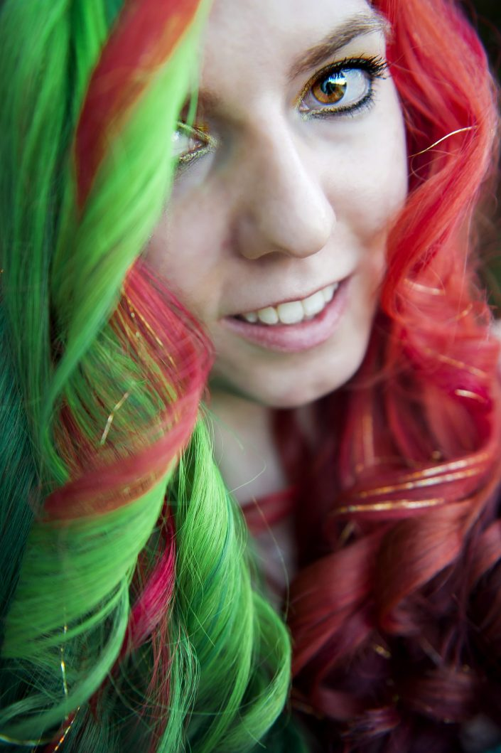 Curled half green and half red hair dyed for Christmas with gold tinsel.