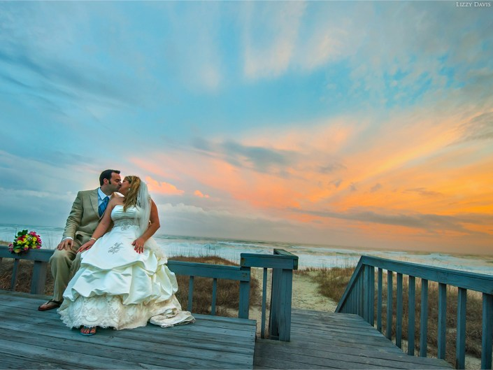 Newlywed couple share a kiss in front of a picturesque sunset over Emerald Isle beach in North Carolina.