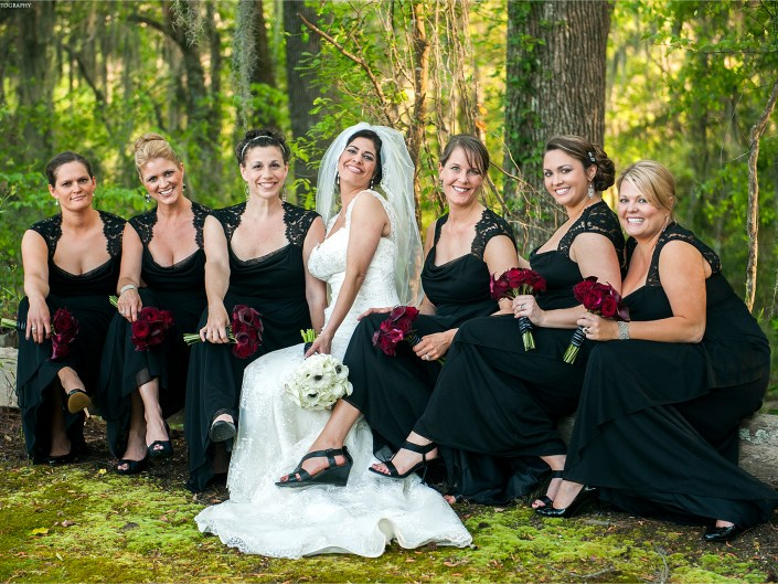 Stunning bride in white contrasting against her bridesmaids black dresses with red rose bouquets.