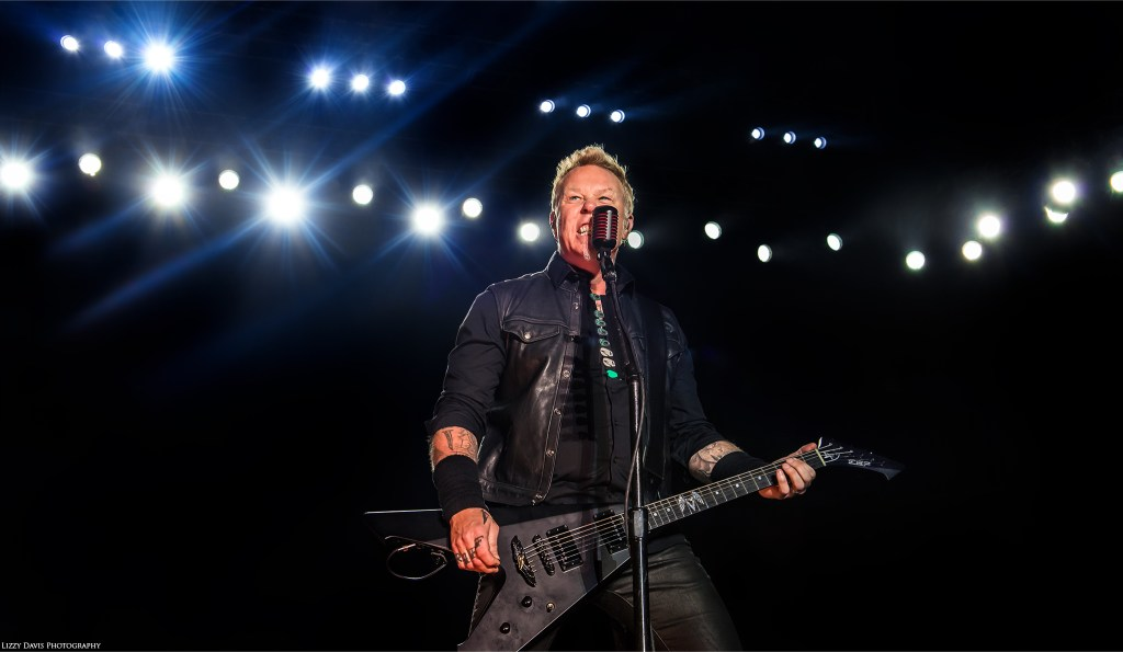 James Hetfield with shining lights behind him at Rock on the Range. Photos of Metallica by ©Lizzy Davis Photography.