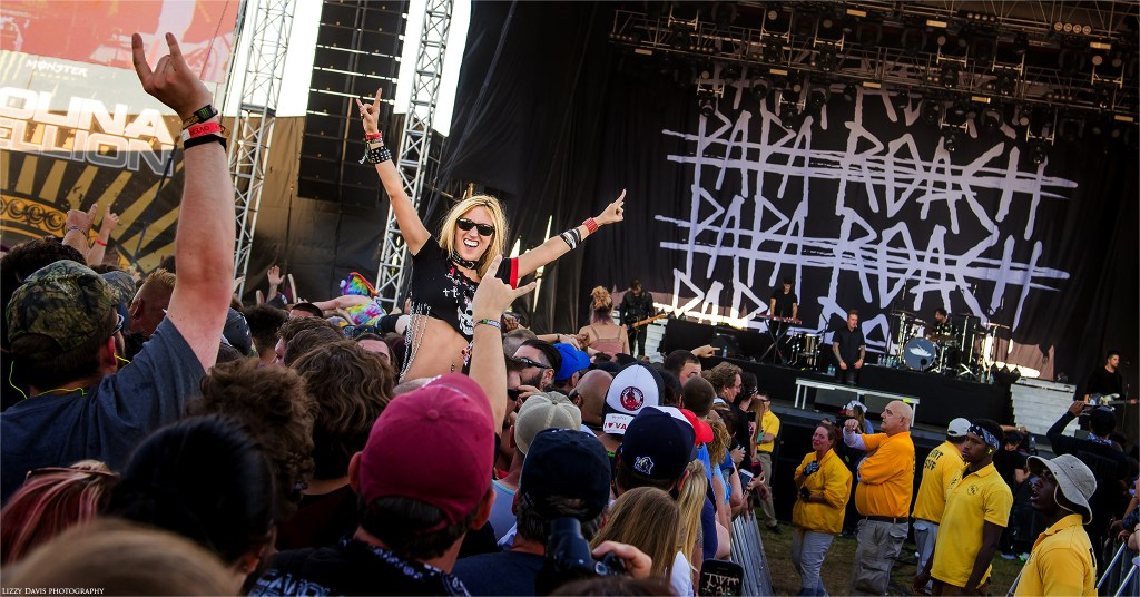 An excited fan sitting on shoulders with her arms up in front of Papa Roach's backdrop at Carolina Rebellion. ©Lizzy Davis Photography