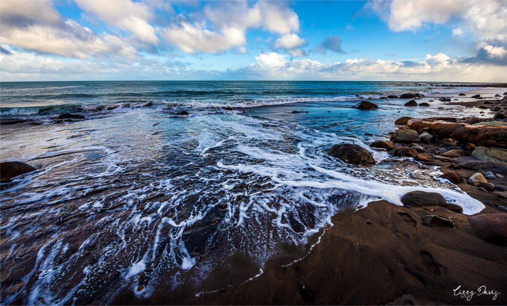 Water on black sand at Ohawe Beach, NZ. | Lizzy Davis Photography