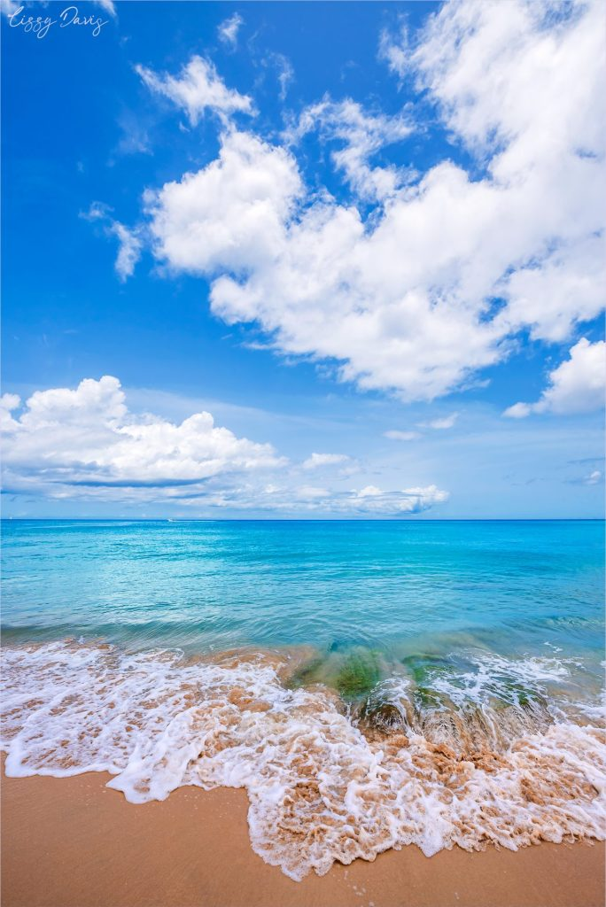 Turquoise blue waters crashing on shore in the morning.