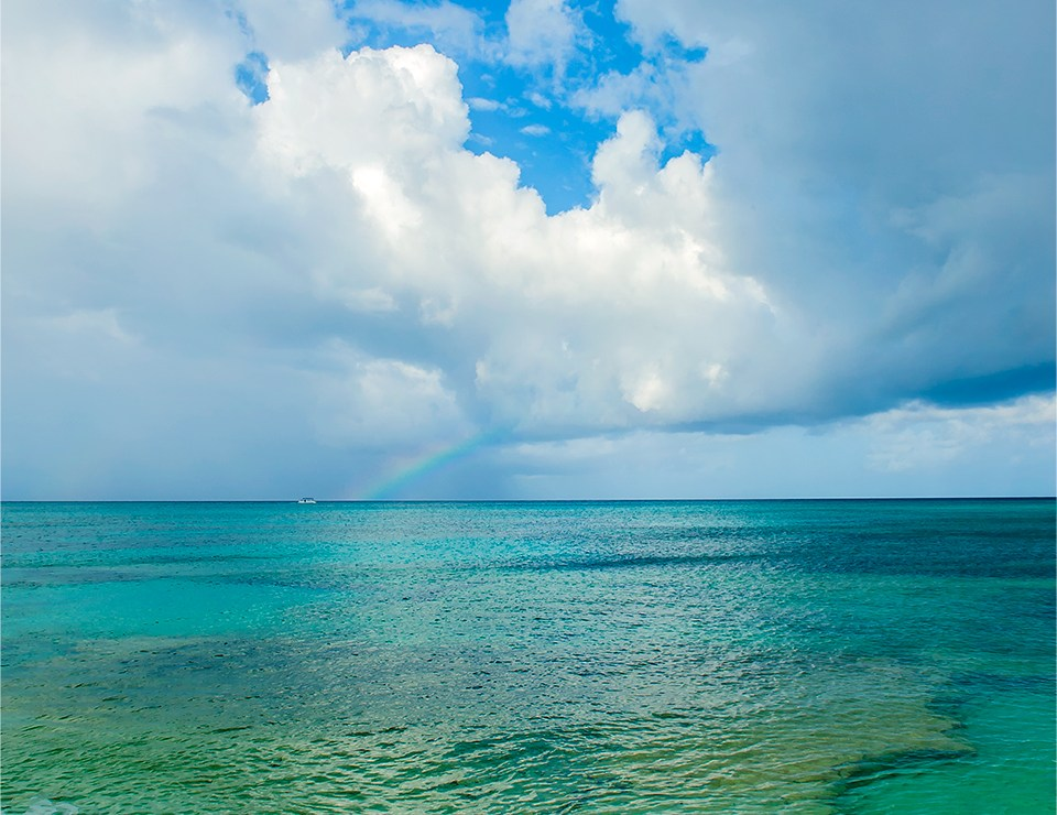 Subtle rainbow over the crystal blue waters of Grand Turk; photo by Lizzy Davis.