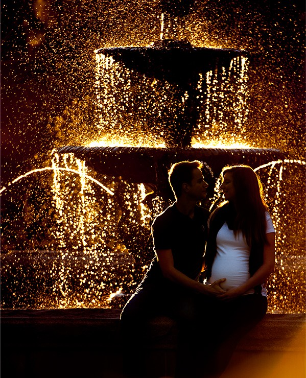 Stunning bokeh photo of a young expecting mother and father in front of a fountain at sunset.