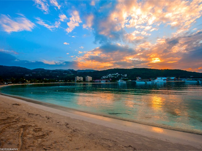 Amazing sunset over turquoise Caribbean waters at Ocho Rios beach in Jamaica by Lizzy Davis Photography.