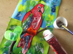 Put P.V.A and ad glitter on parrot and background.