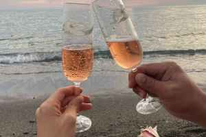 couple clinking glasses of champagne on seashore
