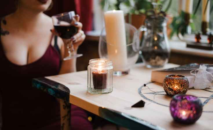 unrecognizable soothsayer with glass of drink at table