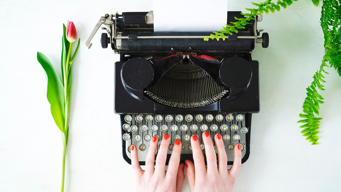 image of Lily's hands at black typewriter, she is wearing orange nail varnish, there is a pink tulip on the desk