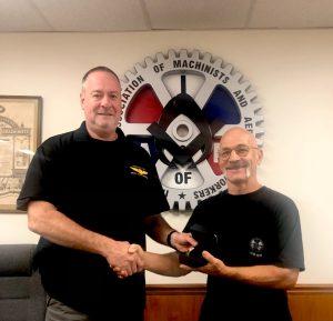 Brian Brinza receives a retirement watch from President Howard Ferguson