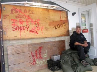 Mark Palazzolo, owner of a bait and tackle shop on the Manasquan Inlet in Point Pleasant Beach, N.J., sits next to wood he has used to board up his business in previous major storms, Sunday, Oct. 28, 2012, in Point Pleasant Beach, N.J