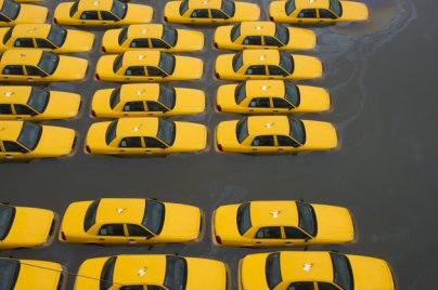Sandy parking lot full of submerged yellow taxi cabs