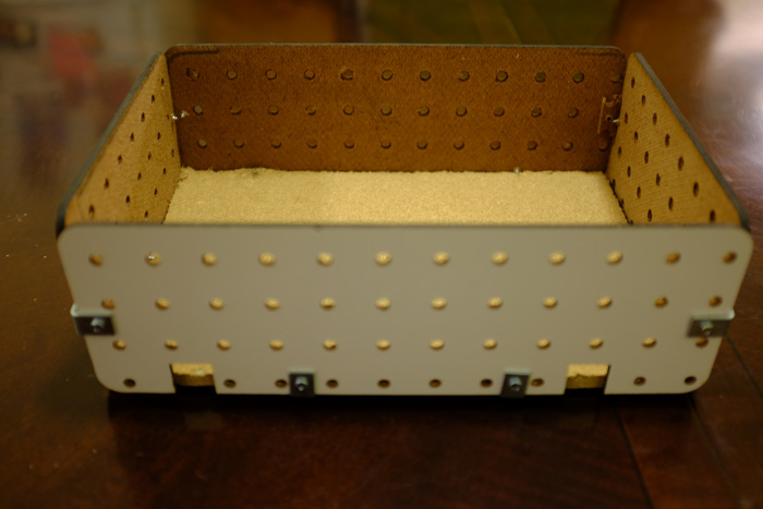 The back has two spaces for larger cords. The holes in the pegboard can be used to bring thin wires into the enclosure.