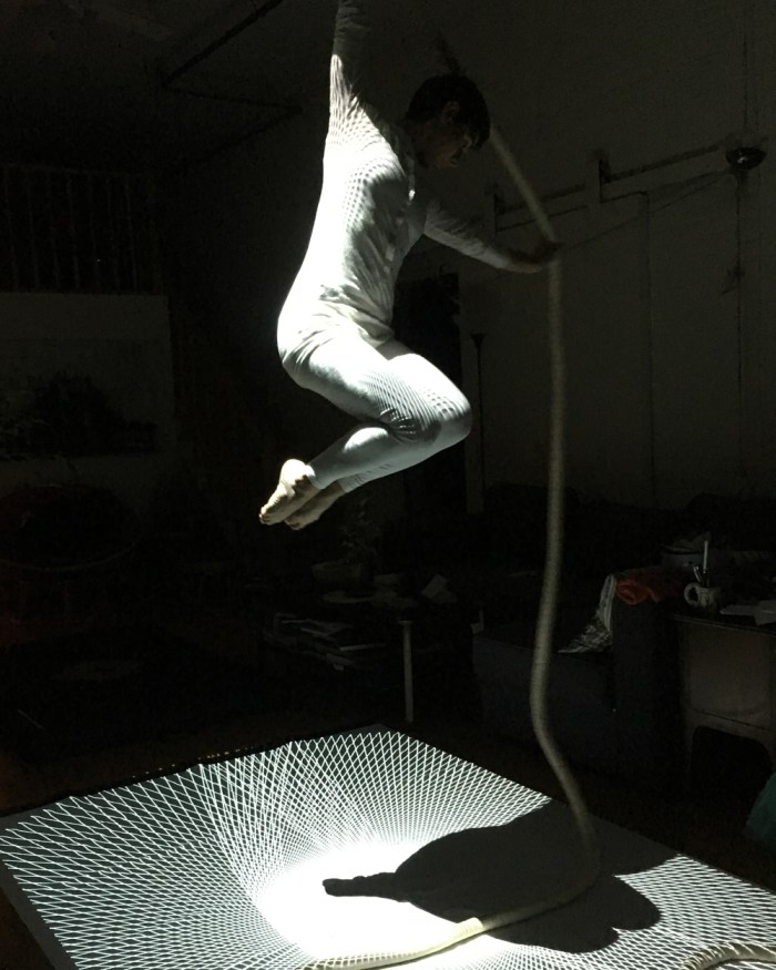 Photo of aerialist transmitting pulse to projection.