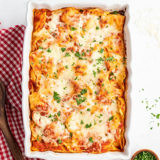A white baking pan full of pasta with a red sauce, and topped with cheese. There is chopped parsley sprinkled on top.