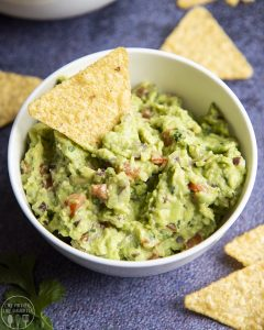 Guacamole in a bowl with a tortilla chip in the middle