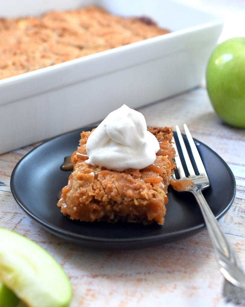 One square of caramel apple bars topped with whipped cream on a brown plate with fork