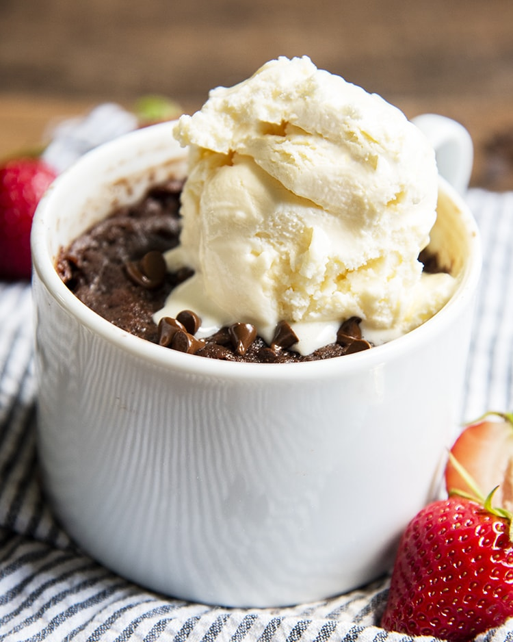A chocolate brownie in a mug with vanilla ice cream melting on top