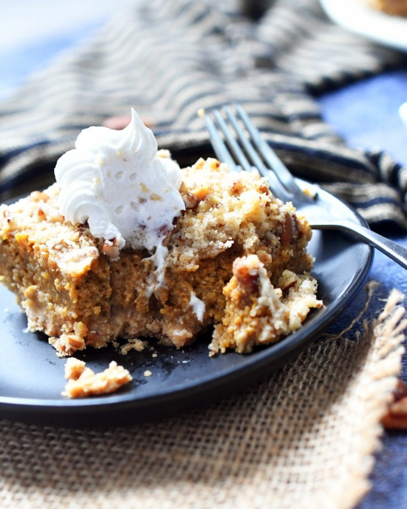 pecan pumpkin cheesecake bar topped with whipped cream on a brown plate with a fork next to it