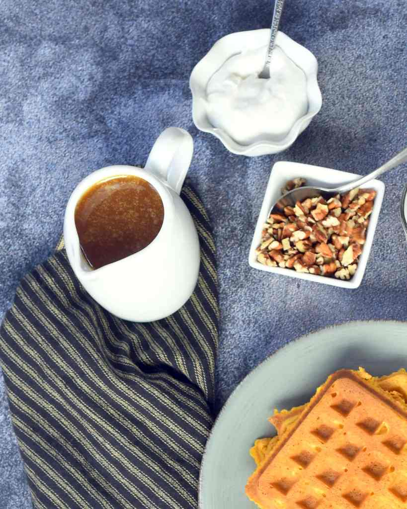 buttermilk syrup in a white pitcher on a brown cloth with pecans and whipped cream in small white dishes next to it