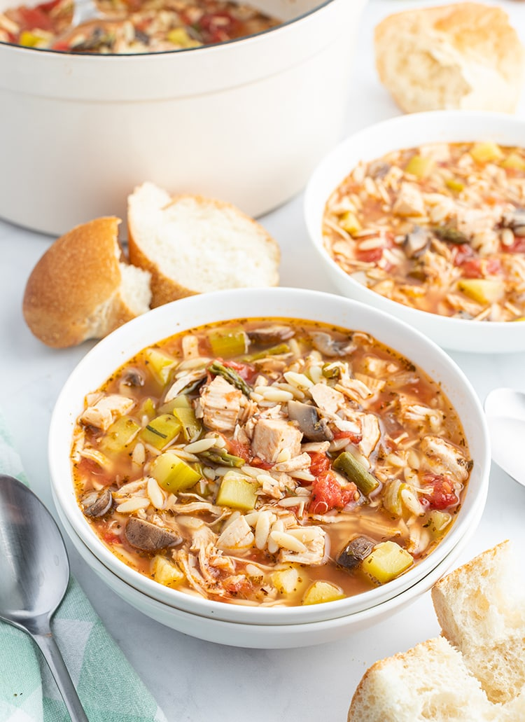 A bowl of turkey and orzo soup with french bread on the side.
