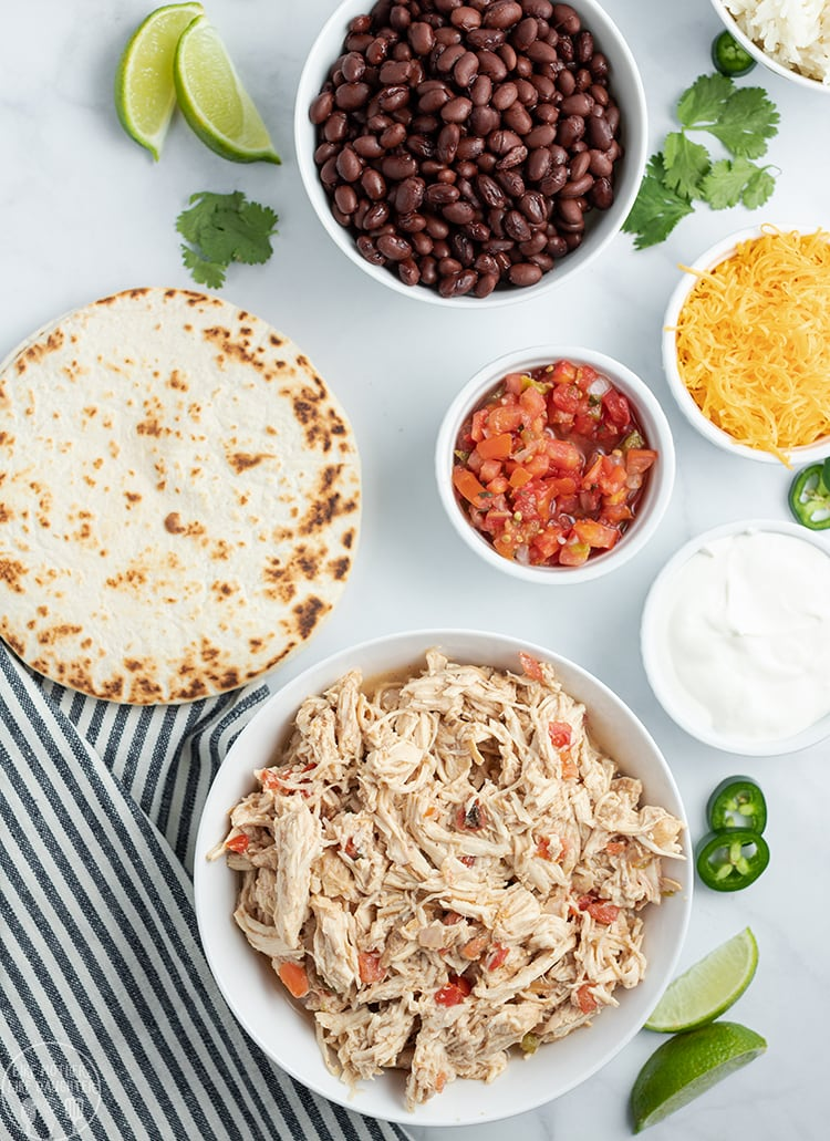 Crockpot Chicken Tacos are perfect with a tortilla and all the taco fixins, black beans, salsa, cheese and more.