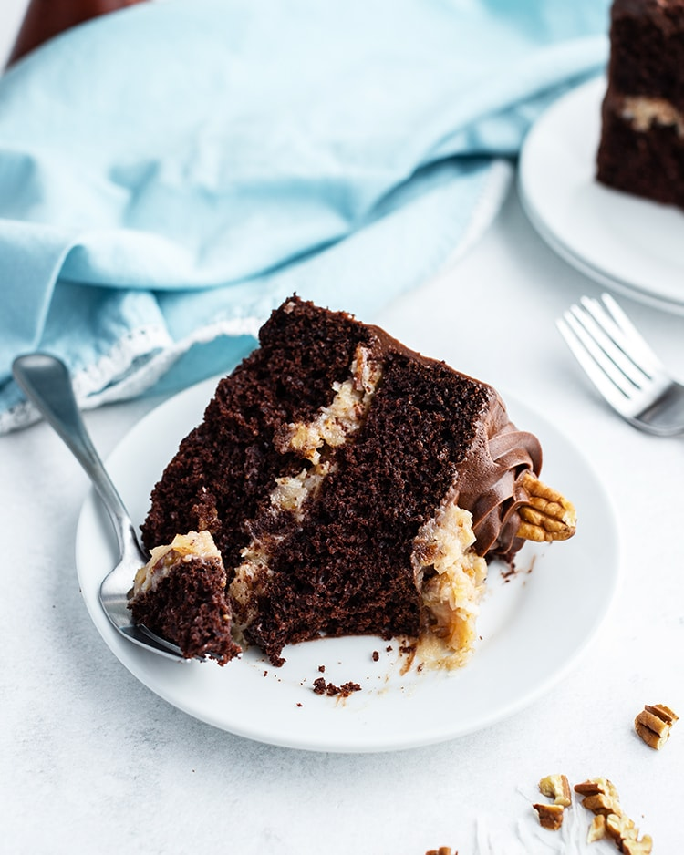 A slice of German chocolate cake with a bite taken out of it.