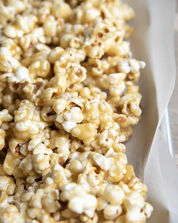 Gooey caramel popcorn in a white bowl