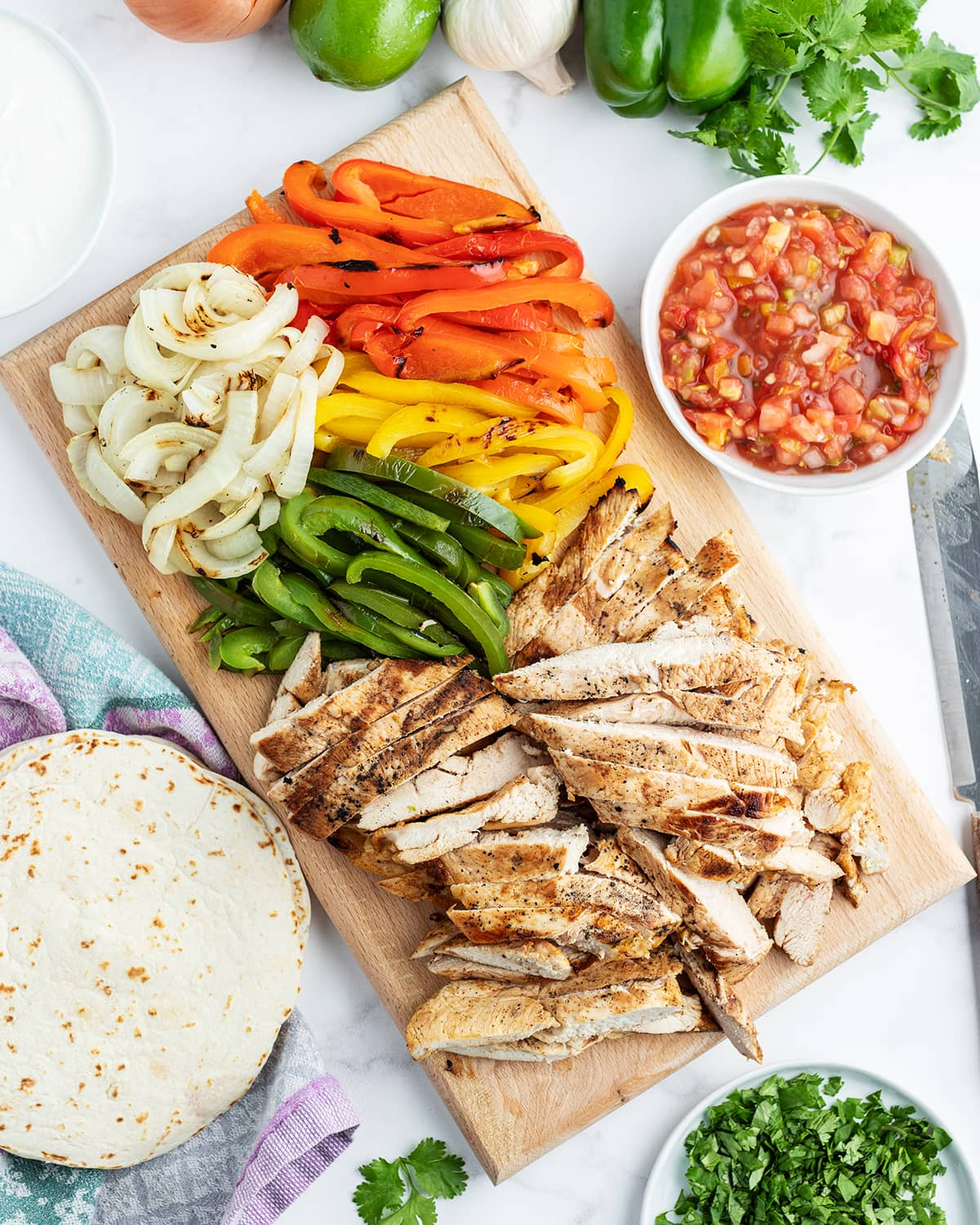 A tray of ingredients for chicken fajitas, with grilled chicken, bell peppers, and onion.