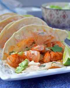 Shrimp taco with yogurt sauce, cilantro, and a side of lime
