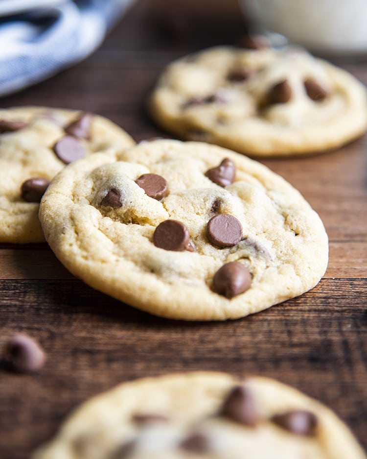 A close up of a chocolate chip pudding cookie leaning on another cookie.