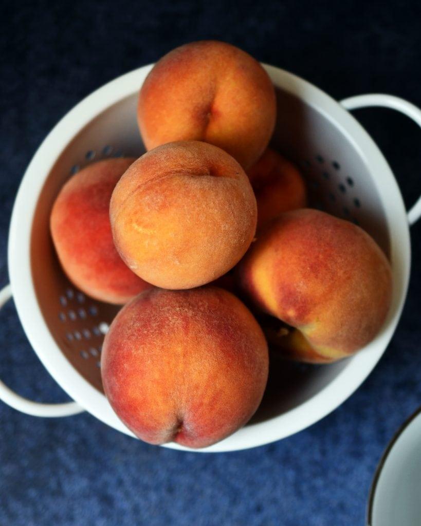 White strainer with fresh peaches