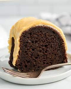 A slice of Chocolate Pumpkin Bundt Cake topped with a pumpkin icing on a plate.
