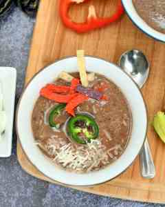 Warm, flavorful black bean soup with a little spicy kick. There are onions, celery, peppers, jalapenos, garlic, broth, cumin, all blended together for a soup to warm your soul.
